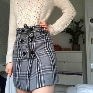 Rutig kjol med knappar och skärp. Använd bara ett fåtal gånger, mycket bra skick. Frakt tillkommer, kan även mötas upp.
