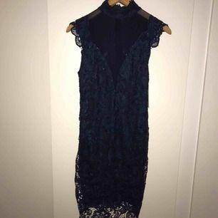Säljer denna cocktail-klänning från Model Behaviour. Har aldrig använt den. Nypris 500kr.Klänningen är ungefär knälång och har en mörk-marinblå färg. Lite högre svinsnygg hals och mörkblå genomskinligt tyg över bröstet. Stenar över spetstyget! Möts i stan