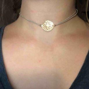 Choker halsband med vitt band och gulddetaljer. Den är 35 cm när man mäter den. Men den är elastiskt. Köparen betalar frakten