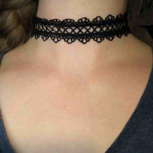 Choker halsband i svart spetts med svarta metall detaljer. Den kan som längst bli 41 cm och som kortast 29 cm. Den är 3 cm tjock. Köparen betalar frakten.