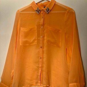 En peach-färgad skjorta med strassdetaljer i storlek 36 från H&M. Använd ett fåtal gånger, mycket gott skick. Möts upp i Stockholm och Uppsala, annars tillkommer frakt