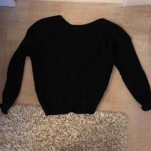 En stickad svart tröja från Nelly med öppen rygg. Nästan aldrig använd.