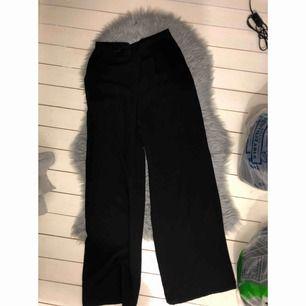 Svarta vida kostymbyxor som aldrig använts men som sitter superfint i midjan och har fint svall ner på benen.