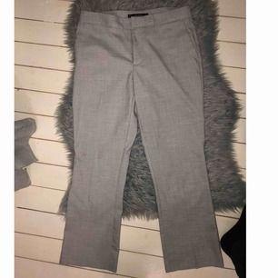 Ljusgråa kostymliknande byxor som är ankellånga och något utsvängda nertill!