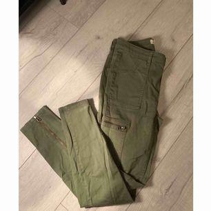 Gröna cargo byxor från H&M med fickor på sidan. Dragkedjor baksida smalben. Använda fåtal gånger. Köparen står för frakt.