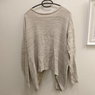 Ljusbrunmelerad stickad tröja från vila. Öppen rygg.