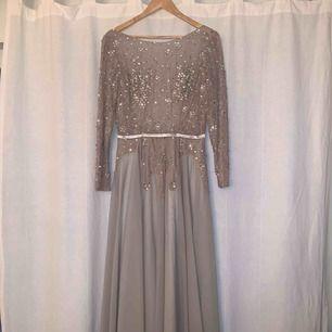 Fantastisk fin balklänning. Aldrig använd!  Öppen rygg och paljett- och glitterdetaljer.  Ljusrosa/beige i färgen men samtidigt lite åt det silvriga hållet.  Jag är 180 cm lång och väger cirka 65 kg. Sitter helt perfekt!