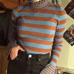 Säljer en riktig glitterbomb från Gina tricot!✨Det är en ribbstickad polotröja som är orange/blå randig med vågig krage, vida muddar och som glittrar, vilket man knappen ser på bilderna men det gör den!⚡️Bara använd 1 gång.