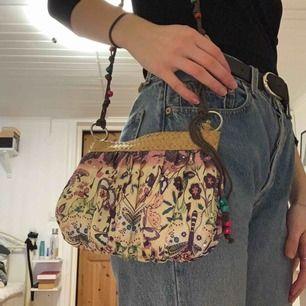 Bohemisk liten väska som varierar i färg mellan lila o gul. Stängs med hjälp av dragkedja. Gott skick. Frakt tillkommer. Kontakta mig vid frågor🥰 (tröjan på bilden går att köpa).