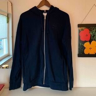 En mörkblå hoodie från Reebok, dragkedja och två fickor på sidorna av hoodien. Fint skick!