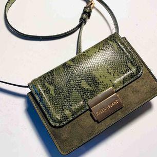 En väska i läderimitation från river island. Grön axelremsväska med gulddetaljer i reptilimitation och mockaimitation. Fins fack för kort i väskan 🦎