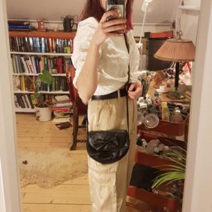 Skitsnygg svart väska med en rosett. Väldigt lång (axelbandetbandet ca. 60 cm) men praktisk pga hur liten den är!