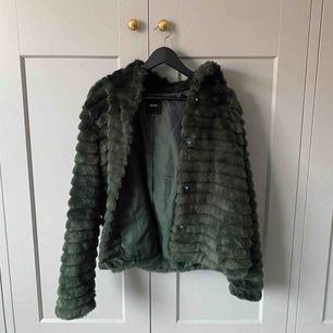 En jacka av skogsgrön fuskpäls införskaffad på vila. Köpt förra året. Jackan har två rymliga fickor, en stor luva och stängs med knappar. Den är knappt använd och därför i bra skick :)