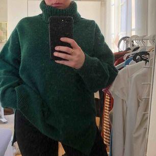 En grön stickad tröja med turtle neck.