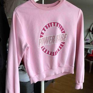 Rosa sweatshirt med muddar & tryck på framsidan. I storlek XS & något croppad från H&M. Använd ett FÅTAL gånger och tryckets kvalitét är som NYTT!