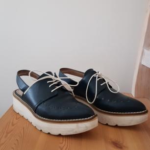 Mörkblå spetsiga skor med lite högre sula, vita snören och hålmönster längs med kanten framtill (se bild 1 och 2). Färgen stämmer överens med verkligheten. Mycket bra skick, använda ett fåtal gånger. Något smutsig vit sula, annars helt rena och fina. Något ingådda. Skickas, frakt tillkommer på 70 kr.