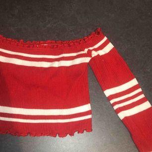 Ribbad, croppad, långärmad, offshoulder röd tröja med vita ränder. Bra skick, mycket stretchigt tyg, 85% viskos och 15% polyester