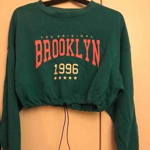 En croppad sweatshirt med åtdragning i midjan. Oversized i storleken och vilken gör färgen rättvis (alltså typ grön blå)z