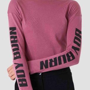 """Rosa/lila långärmad tröja med """"BOY BURN"""" tryck på båda ärmarna från NA-KD! I storlek XXS men skulle säga att den är som en XS. ALDRIG använd och i NYTT skick!"""