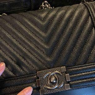 En använd fake Chanel väska OBS lite trasig om man kollar på första bilder där jag pekar, inuti lite trasig där också men kan såklart fortfarande användas därför har jag sänkt priset.