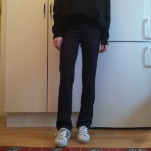 Lätt utsvängda kostymbyxor från Calvin Klein köpta secondhand i stl XS/34. Färgen är typ mörkgrå och byxorna har låg midja. Frakt 42 kr.