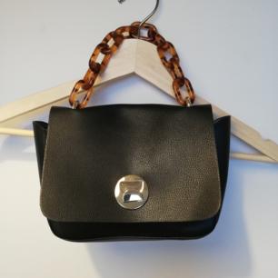Liten svart handväska från Gina Tricot med brunt kedjehandtag. Använd två gånger så i nyskick. Frakt 42 kr.  PS. Säljer byxorna i en annan annons.