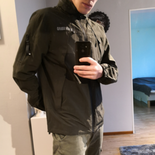 Militärgrön Regnjacka/vindjacka, aldrig använd. Det finns en kapuschong m inbyggd i jackan som går att vika ut vid behov. Skriv vid intresse.  *Köparen står för frakten*
