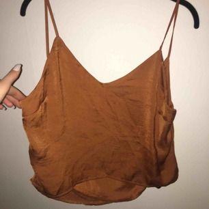 """Kopparfärgat linne som är kortare i modellen, ryggen är en blandning mellan """"cowlneck"""" och """"waterfall"""". Använd en gång."""