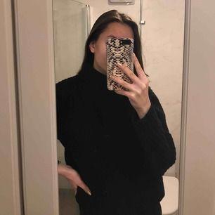 En stickad svart väldigt tjock tröja. Den är riktigt varm och har en 5 cm hög krage. Har aldrig använt den så den är så gott som ny.