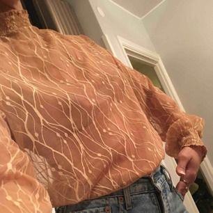 Transparent nude blus i strl M passar L och S beroendes på hur man vill att  dens ska sitta. Den har knappar i halsen bak och smockad polo och ärmslut