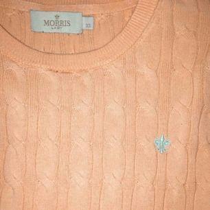 Korallrosa tröja med ljusblått inbroderat tryck från Morris. Nypris 1200kr