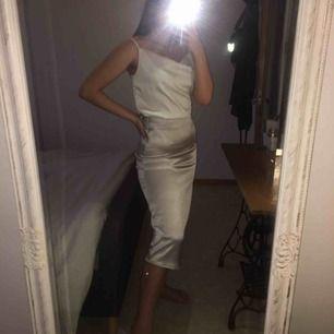 Satin kjol som skimrar silvrigt, tyget är svårt att förklara men fråga gärna efter fler bilder! Den är aldrig använd och har prislappen kvar. Resår i midjan med dragkedja på sidan.