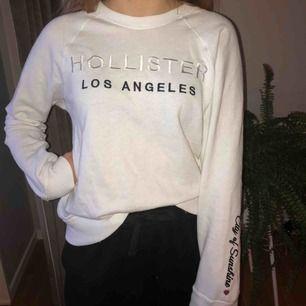 Vit och mjuk tröja från Hollister med silvrig text i storlek S. Köpt för 2 år sedan men använd ett fåtal gånger.