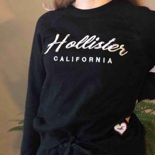 Svart mjuk tröja från Hollister i storlek XS med silvrig text och ett litet hjärta nere i vänstra hörnet.