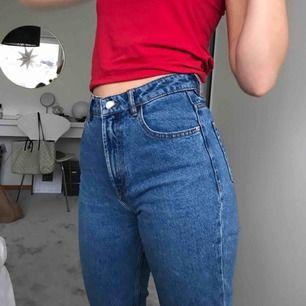 Så fina blå jeans i straightleg/momjeans - modell. 🥰Jättefint skick trots en del användande. Färgen är lika blå som på de första bilderna och tredje bilden visar även att de är rippade vid anklarna.  Bara att höra av dig vid frågor!🌟