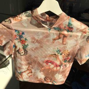 Croppad mesh-tröja med änglar på. Bara testad. Det står att den är i storek M, men skulle säga att den är XS. (:   Möts upp i Uddevalla, annars tillkommer frakt xx