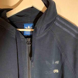 En mörkblå adidas hoodie med dragkedja & fickor! Samt d klassiska 3 ränderna på ärmarna. Väl använd därav sliten & billigt pris!