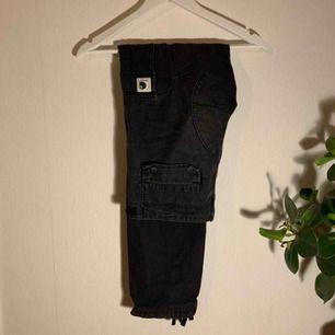 Carhartt Cargo Pants, svarta men nu snyggt urtvättade & mer åt de gråa hållet.  Praktiska fickor, justerbar midja & reglerbara i ändarna på benen.  Knappen i midjan är utbytt & den sitter lite löst men är lätt att sy dit ordentligt igen!
