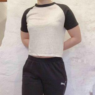 Naturvit croppad tröja med svarta collegeärmar från BikBok