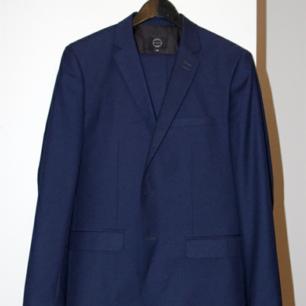 Stilig dansk kostym i marinblått från märket Suit. Använd en gång så i nyskick. Slim fit, storlek 46. Säljs bara pga att jag har gått upp i vikt och byxorna passar ej längre ((