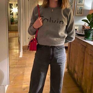 Grå collegetröja från Calvin Klein. Aldrig använd så jättefint skick! Superskönt material. Matchar med det mesta. Unisex till modellen.  Frakt tillkommer