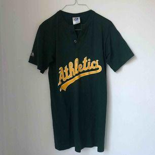 Mörkgrön Athletics t-shirt köpt på Beyond Retro.   Mycket bra skick, använd fåtal gånger.   Möts upp i Stockholm.