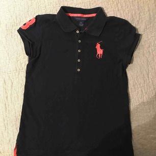 En skit snygg Ralph lauren tröja som är marinblå med rosa detaljer och knappar i mitten av bröstet. Barn storlek:L (13-15) XS i vanlig storlek. Använd fåtals gånger och bra skick. Köparen står för frakt