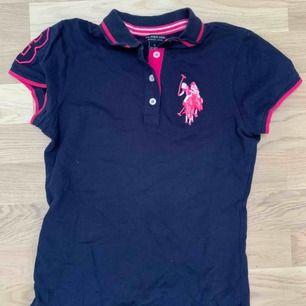 Piké tröja, marin blå med rosa detaljer, köparen står för frakten. Kan mötas upp