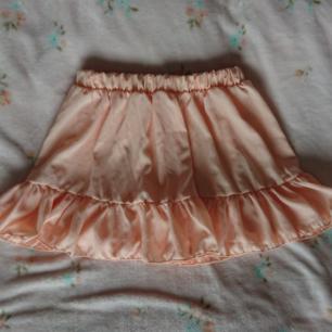 Supersöt persikorosa kort kjol med volang Onesize, resår i midjan, fint skick