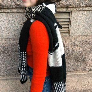 Knitted stretchy long scarf. White and black with gold accent