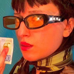 Solglasögon med gult glas och tjocka svarta bågar.