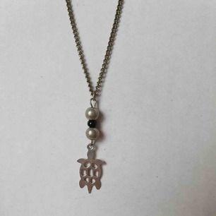Vackert halsband med pärlor och en sköldpadda 🐢 gjort i second-hand material ♻️ OBS! Frakt ingår inte i priset. Om du vill köpa till en papperslåda vi har tillverkat själva tillkommer en extra kostnad på 15kr ✨