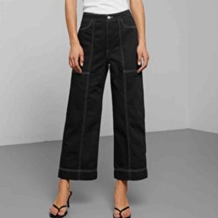 Svarta byxor med vita sömmar från Weekday i modellen Avon. Midja: 74 cm Innerbenslängd: 66 cm. Frakt är gratis!