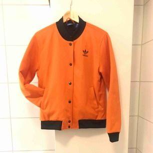 Orange adidas bomberjacka inköpt för 2 somrar sen- sparsamt använd så den är i nyskick. :)  Kan skicka eller mötas upp i Stockholm.  Nypris 900:-